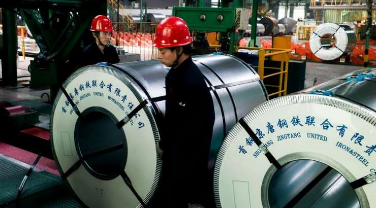 Workers pack steel rolls in a steel factory in China. PHOTO/AFP