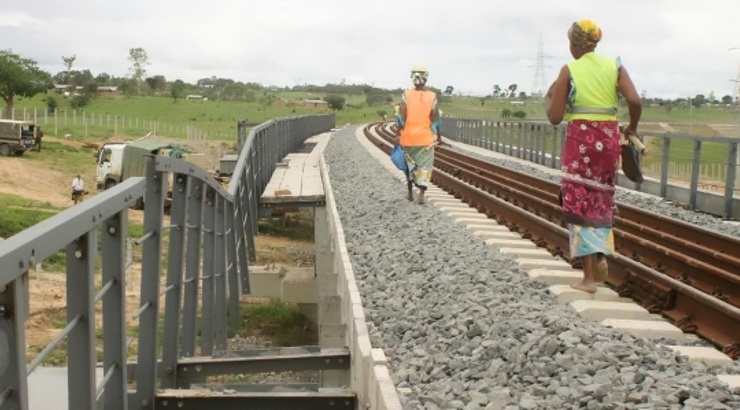 Workers pass by a vandalised section of the Kenya sgr.